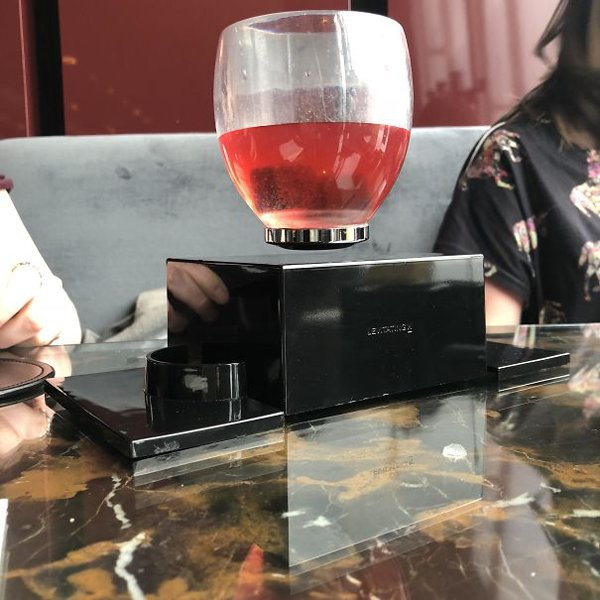 The glass of beverage can be seen in the air by modern technology in another restaurant.