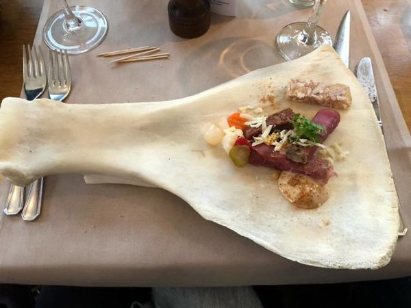 A very large bone is presented with a little meal and this strange dish is also a way to impress people.